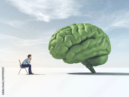 Man looking at a green brain in a field.
