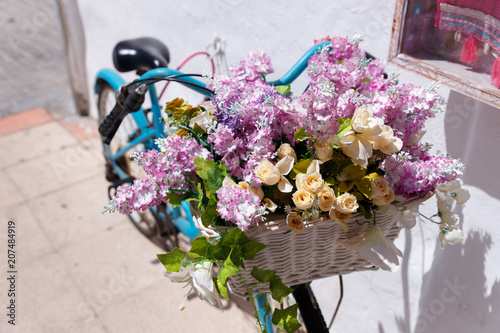 Fotobehang Fiets A bicycle with flowers in a basket near the store in spain.