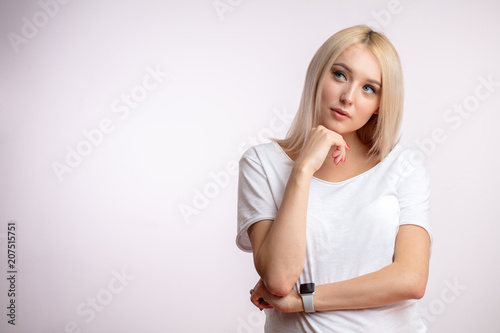 Leinwanddruck Bild thoughtful young blonde with hand on chin. girl is lost in reverie