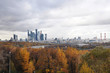 Autumn city with the city towers and colourful forest. Rainy foggy day in Moscow above the river.