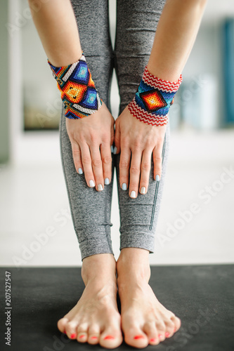 Fotobehang School de yoga Yoga instructor put her hands witn wristbands near her feet on mat, close up