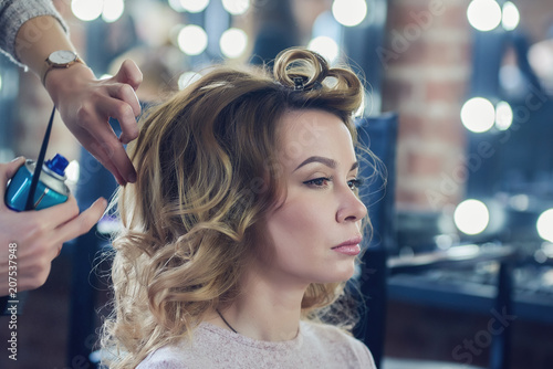 Young european woman is getting proffessional hair style in a beauty salon.