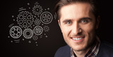 Portrait of a young businessman with rotating gears next to him on a dark background - 207544727