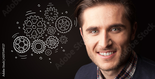 Leinwanddruck Bild Portrait of a young businessman with rotating gears next to him on a dark background