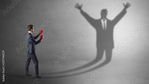 Leinwanddruck Bild Businessman with boxing gloves fighting with disarmed businessman shadow