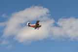 old orange biplane flying in a blue sky with clouds