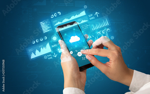 Leinwanddruck Bild Female hand using smartphone with financial tracking concept illustrated by graphs and symbols