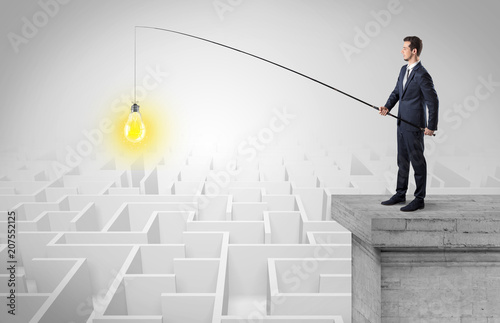 Leinwanddruck Bild Young businessman fishing new idea concept on the top of a building from a maze