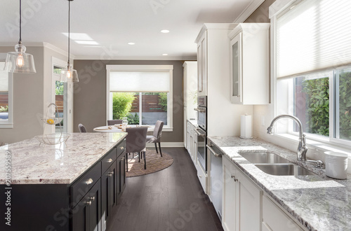 Beautiful Kitchen in New Luxury Home with Island, Oven, Range, Stainless Steel Appliances, and Refrigerator