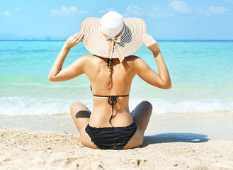 Attractive young lady relaxing and loking at the clear ocean