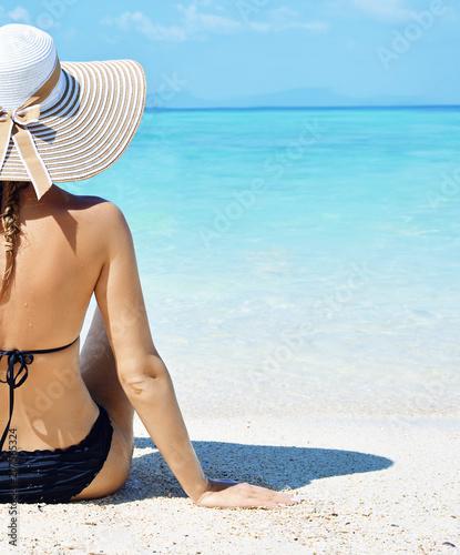 Foto Murales Sensual woman relaxing on a tropical beach