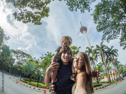 Fotobehang Kuala Lumpur happy family makes selfie in the background of the Minar tower in Kuala Lumpur