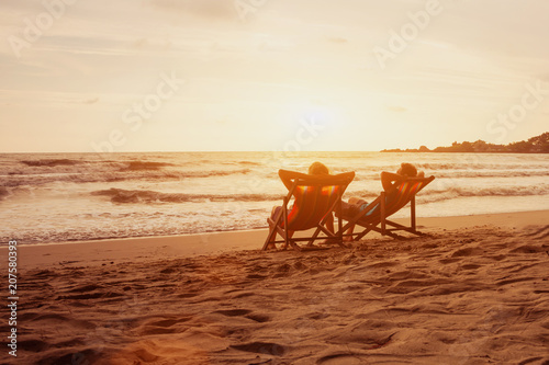 Leinwanddruck Bild Tourism and travel vacation. Senior happy couple relaxing in luxurious resort sunset beach in deck chairs. Romantic honeymoon holidays. Recreation concept with copyspace.