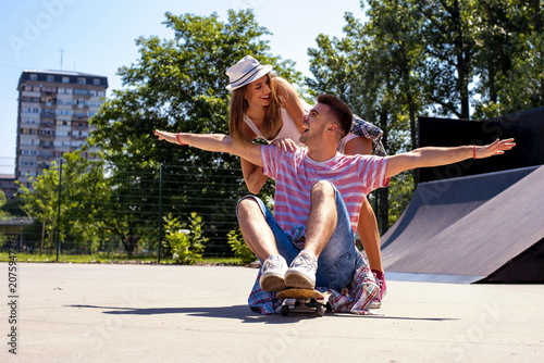 Fotobehang Skateboard Happy young couple having fun with skateboard in the skate park