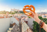 A female hand holds a traditional bakery and a pretzel delicacy against the background of the historic center of the European city