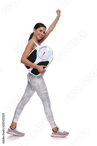 attractive woman walking to side and celebrating weight loss