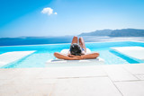 woman at an infinity pool looking out over the caldera of  Santorini Greece, luxury vacation - 207623531