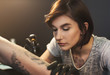 Leinwanddruck Bild - A professional tattooer artist doing picture on man hand