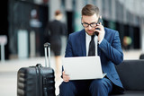 Busy agent in suit sitting in lounge of airport, making working calls and looking through online data in laptop - 207646355