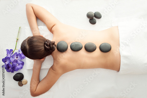 Stone treatment. Top view of beautiful young woman lying on front with spa stones on her back.  Beauty treatment concept. - 207651525