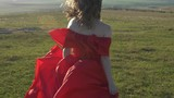 A young woman in a scarlet dress with bare shoulders running to the horizon - 207654776