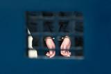 Prisoner in handcuffs behind bars - 207659565