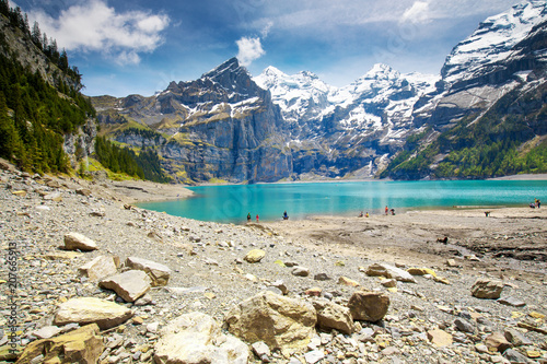 Amazing tourquise Oeschinnensee lake with waterfalls, wooden chalet and Swiss Alps, Berner Oberland, Switzerland - 207665913
