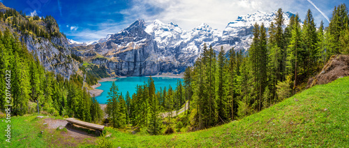 Amazing tourquise Oeschinnensee lake with waterfalls, wooden chalet and Swiss Alps, Berner Oberland, Switzerland - 207666122