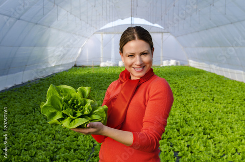 Leinwanddruck Bild Happy beautiful young woman standing in green house and holding lettuce