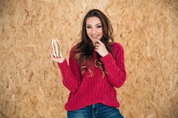 Studio photo on an isolated brown background model cheerfully and broadly smiling, wore a light sweater and blue wide jeans, holds a large appetizing sandwich in her hand, put her hand to her face © romannoru