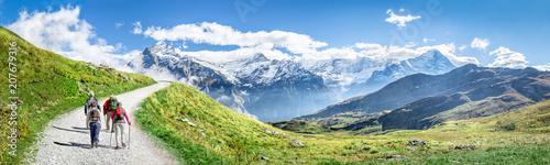 Leinwanddruck Bild Gruppe beim Wandern in den Schweizer Alpen als Panorama Hintergrund