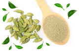 Green cardamom seeds and powder in a wooden spoon isolated on white background decorated with leaves. Top view. lay flat - 207684729