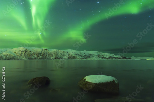 Fotobehang Noorderlicht Northern lights Aurora borealis at the lakeside with rocks of a fjord during low tide in a snowy winter landscape with mountains