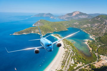 Airplane is flying over islands and sea at sunrise in summer. Landscape with white passenger airplane, seashore, mountains, sky, and blue water. Blue passenger aircraft. Travel and resort. Tourism