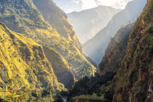 Fotobehang Bergrivier Colorful landscape with high Himalayan mountains, green forest, blue sky with clouds and yellow sunlight at sunrise in summer in Nepal. Mountain valley in the morning. Travel in Himalayas. Nature