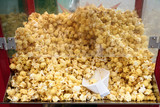 sweet popcorn and shovel in a popcorn machine shop - 207689967
