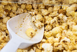 fresh sweet popcorn and shovel in a popcorn machine, close up - 207690148