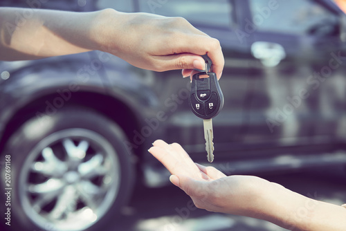 Woman's hand give the car key and blurred background.
