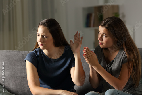 Leinwanddruck Bild Woman begging forgiveness and friend ignoring her