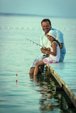 Father with his daughter fishing in a sea on a wood pier at sunset. - 207705169