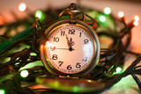 clock on a chain in the lights of a garland. The time on the clock 11:55 PM - 207711719