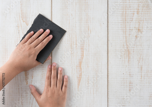 Sanding and smoothing wood with black sandpaper - 207712772