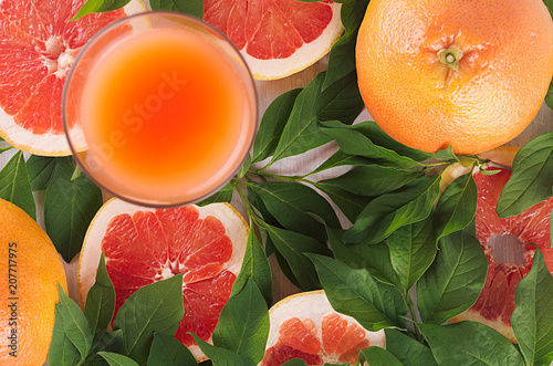 Aluminium Sap Pink grapefruits juice in elegant glass and grapefruits with green leaf, macro, top view. Summer fruit fresh background.
