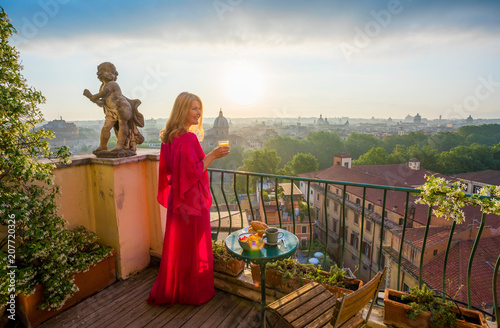 Woman standing on balcony with glass of fresh orange juice
