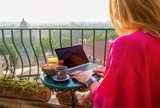 Woman using laptop during breakfast on balcony - 207720516