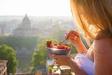 Woman having delicious healthy breakfast on terrace in city - 207721395