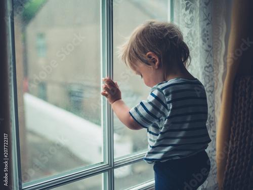Foto Murales Little boy by window