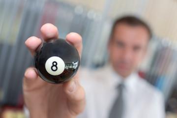 player holding a billard 8-ball