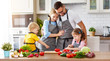 Leinwanddruck Bild - happy family with children preparing vegetable salad .