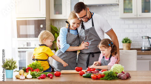 Leinwanddruck Bild happy family with children preparing vegetable salad .